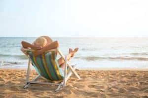 Rust vrouw op strandstoel op strand relaxen