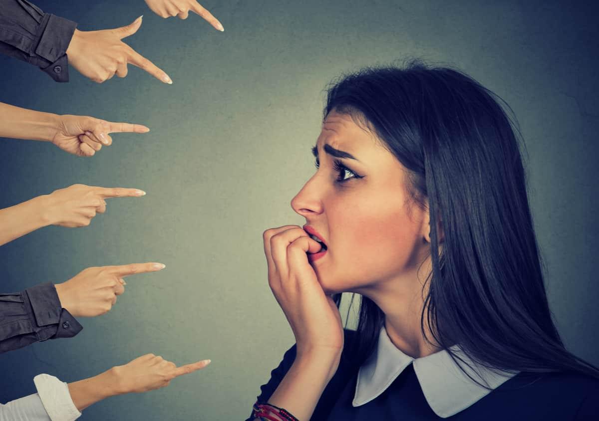 Vrouw last van faalangst. Bang. Wijzende vingers. Geen fouten durven maken.